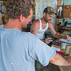 """Ernie Wallace (foreground), captain of """"Reel Catch"""", and Ryan Schultz (co-op employee) record a transaction at the Friendship Lobster Co-op in Friendship, Maine."""