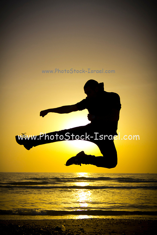 Silhouette of a man shadow fighting on the beach at sunset