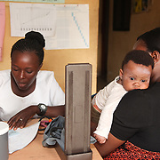 INDIVIDUAL(S) PHOTOGRAPHED: From left to right: Adetona Olubunmi, Chew, and Nkechi Jerome. LOCATION: Ikeja Primary Health Care Center, Lagos, Nigeria. CAPTION: After examining Nkechi Jerome's baby, Chew, nurse Adetona Olubunmi writes out a prescription for the infant at the Ikeja Health Center.
