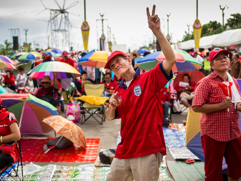 17 MAY 2014 - BANGKOK, THAILAND:  A Red Shirt supporter dances on Aksa Road in Bangkok during the Red Shirt rally. Thousands of Thai Red Shirts, members of the United Front for Democracy Against Dictatorship (UDD), members of the ruling Pheu Thai party and supporters of the government of ousted Prime Minister Yingluck Shinawatra are rallying on Aksa Road in the Bangkok suburbs. The government was ousted by a court ruling earlier in the week that deposed Yingluck because the judges said she acted unconstitutionally in a personnel matter early in her administration. Thailand now has no functioning government. Red Shirt leaders said at the rally Saturday that any attempt to impose an unelected government on Thailand could spark a civil war. This is the third consecutive popularly elected UDD supported government ousted by the courts in less than 10 years.   PHOTO BY JACK KURTZ