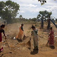 The parents of students help clean the grounds of the Thikilivattai Government Tamil Mixed School in Batticaloa District. <br /> <br /> Thikilivattai Government Tamil Mixed School reopened in May 2008 after local conflict between the LTTE and SLA  troops eased. There are now 351 students in grades 1-9 with a teaching staff of 18. The school has no water supply. Though many of the pupils' parents are not well educated themselves (most are employed in casual paddy cultivation, fishing and seasonal day-wage labour), there is a parents' mobilisation committee that encourages pupil attendance and is involved in helping keep the school clean. The school has an active sports department. Many of the students suffer with the trauma and stress associated with those living in conflict situations. The staff must deal with these issues as well as the personal difficulties that they themselves suffer living in a conflict environment. UNICEF have provided three temporary learning spaces to make up for the lack of space in the original school building. A further two classes must be accommodated beneath trees. UNICEF have also supplied the school furniture.<br /> <br /> Photo: Tom Pietrasik<br /> Batticaloa District, Sri Lanka<br /> September 30th 2009