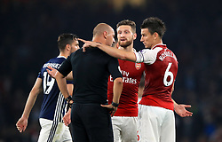 Arsenal's Shkodran Mustafi and Arsenal's Laurent Koscielny speak with referee Robert Madley