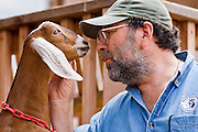 July 26, 2008 -- SNOWFLAKE, AZ: DAVID HEININGER talks to one of his kids (baby goat) on the Black Mesa Ranch, a 280 acre spread in the high desert near Snowflake, AZ. The ranch owners, David and Kathryn Heininger, run a herd of about 40 Nubian dairy goats and hand make artisan cheese from the goat's milk. It's a second gear for them, they retired from Tucson, AZ, where they bought and renovated  historic homes. The moved to the ranch in 2001 and started making and selling cheese shortly after the move. Their cheese is used in expensive restaurants in Phoenix and sold at natural food stores in Arizona.   PHOTO BY JACK KURTZ