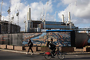 People pass by a hoarding near the redevelopment of Battersea Power Station and its surroundings on 1st February 2020 in London, England, United Kingdom. Battersea Power Station is a decommissioned coal-fired power station located on the south bank of the River Thames, in Nine Elms, Battersea, an inner-city district of South West London. Now a well advanced construction site and under development, the site will become both residential and commercial property.