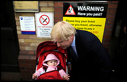 London Mayor Boris Johnson with a baby at a train station during the Mayoral Campaign, London, UK, April 13, 2012. Photo By Andrew Parsons / i-Images.