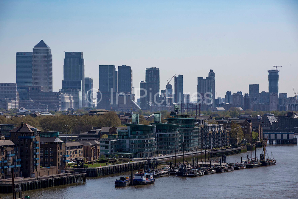 A view down the River Thames towards, Hermitage Community Moorings, Wapping High Street,  Canary Wharf and the Isle of Dogs. London UK.