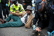 Glued on protester has his hand freed by police during Extinction Rebellion disruption outside City Airport on 10th October 2019 in London, England, United Kingdom. The protest is against the climate and pollution impact of the government's plans for airport expansion which will potentially double the amount of flights coming from City Airport. Extinction Rebellion is a climate change group started in 2018 and has gained a huge following of people committed to peaceful protests. These protests are highlighting that the government is not doing enough to avoid catastrophic climate change and to demand the government take radical action to save the planet.
