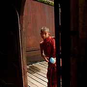 Novice monk looking inside Shwe Yan Pya monastery