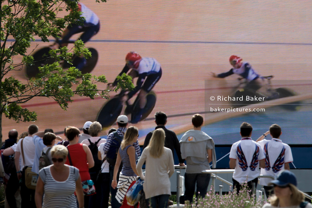Seen on a large TV screen and watched by gasping spectators is the ill-fated heat of the British cycling team (Philip Hindes, Jason Kenny and Sir Chris Hoy) which was restarted after one rider's bike malfunctioned during the London 2012 Olympics. The British team went on to win gold a little later. This land was transformed to become a 2.5 Sq Km sporting complex, once industrial businesses and now the venue of eight venues including the main arena, Aquatics Centre and Velodrome plus the athletes' Olympic Village. After the Olympics, the park is to be known as Queen Elizabeth Olympic Park.