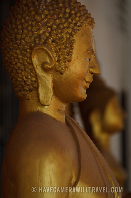 Golden statue of The Buddha at a Wat (Buddhist Temple) in Vientiane, Laos. This statue is in the Cambodian style. Side view.
