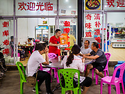 """14 FEBRUARY 2019 - SIHANOUKVILLE, CAMBODIA:  A Chinese waiter takes orders from a table of Chinese diners in a restaurant in Sihanoukville. There are thousands of Chinese workers in Sihanoukville who work to support the casino and hotel industry in the town and thousands of other Chinese migrants have moved into Sihanoukville and opened businesses that cater to the workers. There are about 80 Chinese casinos and resort hotels open in Sihanoukville and dozens more under construction. The casinos are changing the city, once a sleepy port on Southeast Asia's """"backpacker trail"""" into a booming city. The change is coming with a cost though. Many Cambodian residents of Sihanoukville  have lost their homes to make way for the casinos and the jobs are going to Chinese workers, brought in to build casinos and work in the casinos.      PHOTO BY JACK KURTZ"""