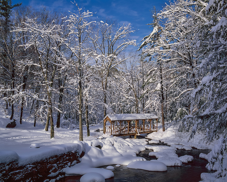 Robert Hebb memorial bridge, covered footbridge in snowy winter forest, Willard Brook State Forest, Ashby, MA