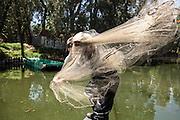Un pescador lanza una atarraya de pesca en los canales de Xochimilco. La introducción de tilapia produjo depredación y reducción de población del ajolote local.<br />  27 de marzo de 2014. (Foto: Prometeo Lucero)