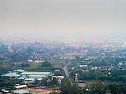 "06 APRIL 2013 - CHIANG MAI, CHIANG MAI, THAILAND: The view from the scenic overlook at Wat Phra That Doi Kham (Temple of the Golden Mountain) in Chiang Mai is obscured by smoke from illegal burning going on around the city. The ""burning season,"" which roughly goes from late February to late April, is when farmers in northern Thailand burn the dead grass and last year's stubble out of their fields. The burning creates clouds of smoke that causes breathing problems, reduces visibility and contributes to global warming. The Thai government has banned the burning and is making an effort to control it, but the farmers think it replenishes their soil (they use the ash as fertilizer) and it's cheaper than ploughing the weeds under.   PHOTO BY JACK KURTZ"