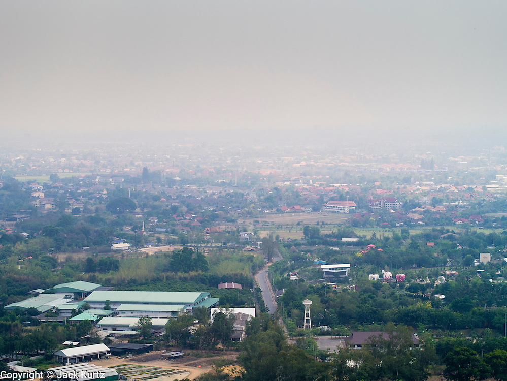 """06 APRIL 2013 - CHIANG MAI, CHIANG MAI, THAILAND: The view from the scenic overlook at Wat Phra That Doi Kham (Temple of the Golden Mountain) in Chiang Mai is obscured by smoke from illegal burning going on around the city. The """"burning season,"""" which roughly goes from late February to late April, is when farmers in northern Thailand burn the dead grass and last year's stubble out of their fields. The burning creates clouds of smoke that causes breathing problems, reduces visibility and contributes to global warming. The Thai government has banned the burning and is making an effort to control it, but the farmers think it replenishes their soil (they use the ash as fertilizer) and it's cheaper than ploughing the weeds under.   PHOTO BY JACK KURTZ"""