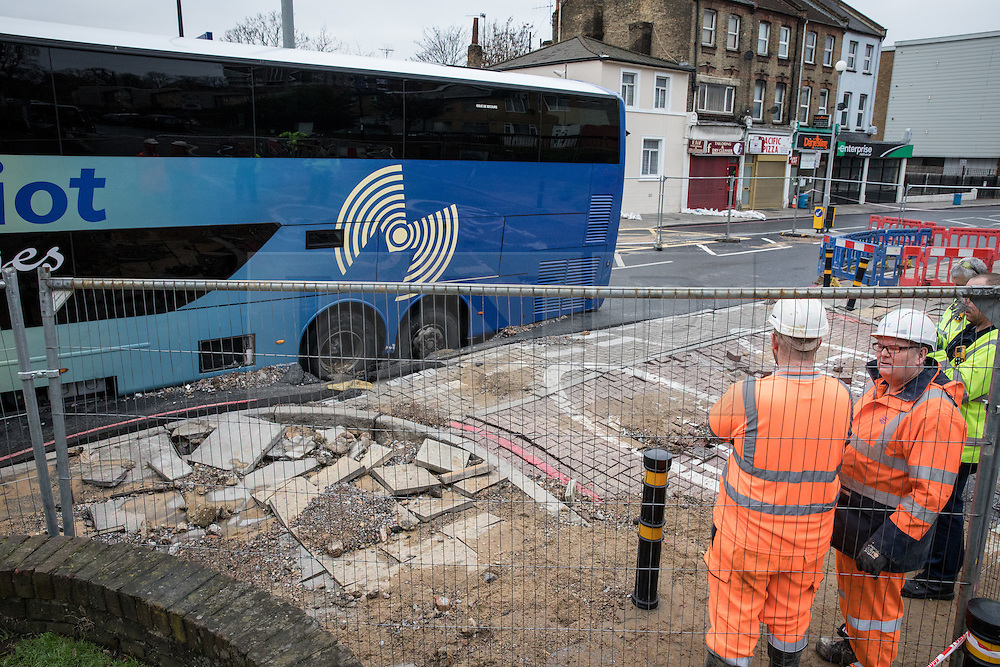 © Licensed to London News Pictures. 27/11/2016. London, UK. Contractors work to seal the gas and water mains after a tourist coach fell into a sinkhole in Lewisham. Lee High Road has been closed off and police declared a 'major incident' after the coach with 100 passengers on board fell into a sinkhole caused by a burst water mains, flooding a long stretch of the road including many local businesses. . Photo credit: Rob Pinney/LNP