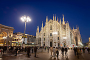 Crowds of people walk in front of the Cathedral in Piazza del Duomo as night falls in central Milan on 8th December 2008 in Milan, Italy. The cathedral, or duomo took six centuries to build and occupies the heart of the city, and attracts visitors from all over the world.
