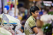 09 OCTOBER 2012 - BANGKOK, THAILAND: A vendor waits for a customer at his booth in the Bangkok Flower Market. The Bangkok Flower Market (Pak Klong Talad) is the biggest wholesale and retail fresh flower market in Bangkok. It is also one of the largest fresh fruit and produce markets in the city. The market is located in the old part of the city, south of Wat Po (Temple of the Reclining Buddha) and the Grand Palace.    PHOTO BY JACK KURTZ