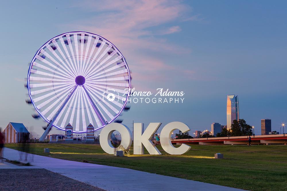 People ride the Wheeler District Wheeler Wheel along the Oklahoma River in Oklahoma City, Tuesday, July 5, 2016. The Wheeler Wheel is the former Santa Monica Pier ferris wheel.  (Photo copyright © 2016 Alonzo J. Adams)