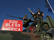 A Trump supporter stands on top of a repurposed troop carrier during a rally protesting the results of the presidential vote count.
