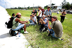 29 August 2006. New Orleans, Louisiana. Lower 9th ward. The media swarm around a woman sat crying beside the newly renovated industrial canal levee flood wall. Civilians gathered at the site of the breach of the industrial canal for the Great Flood commemoration and memorial ceremony to 'honor and remember our loved ones who have passed.' People came to mark the anniversary of devastating hurricane Katrina at the site where the now repaired and allegedly in theory stronger levee flood wall. The levee breached along the industrial canal at the point where people gathered, needlessly killing hundreds of innocent civilians in the worst engineering disaster in US history.<br /> Photo Credit©; Charlie Varley/varleypix.com