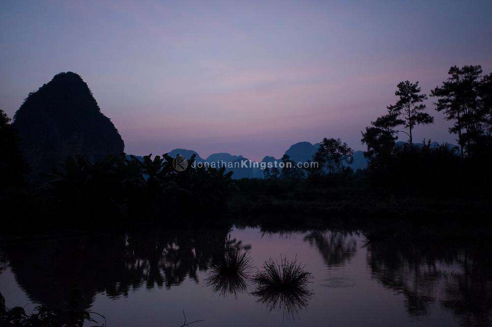 Silhouettes of Karst formations in evening light over a pond of water near Yangshuo, China.
