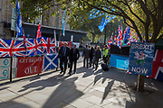 On the day that the EU in Brussels agreed in principle to extend Brexit until 31st January 2020 aka Flextension and not 31st October 2019, passers-by walk alongside Brexiteer flags and banners during a Brexit protest outside parliament, on 28th October 2019, in Westminster, London, England.