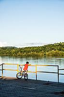 Menino sobre bicicleta olhando para o Rio Uruguai na Praça do Porto. Mondaí, Santa Catarina, Brasil. / <br /> Boy on a bicycle looking at Uruguai River at Port Square. Mondaí, Santa Catarina, Brazil.