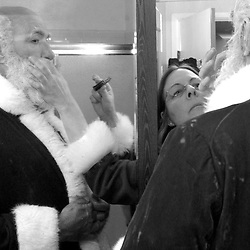 Helped by his partner Michelle Robelet, Russell Bissonnette recieves the final touches of make up on his cheeks before his evening performance at the Miramar Beach Restaraunt Christmas party. Bissonnette has been a professional Santa for nearly 30 years. He started working for Western Temp in 1975, a hiring service for retail store Santas. Bissonnette's first job was at the Hillsdale Mall Macys...Photo by David Calvert<br />