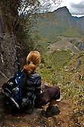 A traveler id havis a rest and admiring the citi of Machu picchu