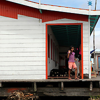 South America, Brazil, Amazon. Young girl curious about the passing boat on the Amazon.