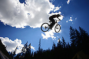 SHOT 8/1/08 3:22:35 PM - A mountain biker silhouetted against the clouds and sky during the Crankworx Colorado Slopestyle Best Trick competition at Trestle Bike Park in Winter Park Resort. The event is a Pro-am mountain bike competition featuring super downhill, slopestyle, big air best trick, cross country and dual slalom events where top pros competed for more than $30,000 in prizes. The event is the only U.S. qualifier for Kokanee Crankworx in Whistler, British Columbia (Aug. 9-17)..Best Trick Results for Crankworx Colorado:.Section 1 Best Trick: Greg Watts - Back Flip Double Bar Spin.Section 2 Best Trick: Cam McCaul - Back Flip Superman.Section 2 Best Trick combination in the Red Bull Section: Andrew Taylor - Back Flip (step-down jump) - Tail Whip over-channel (quarter pipe) - 360 off (quarter pipe deck).(Photo by Marc Piscotty / © 2008)