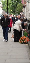 © Licensed to London News Pictures. LONDON, UK  07/07/11. A member of the public lays flowers at the Tavistock Square Memorial. The memorial remembers the 14 people who died on July the 7th 2005 at 09:47 when suicide bomber Hasib Hussain detonated his bomb on the Number 30 bus passing by the spot. The attack was one of 4 that were set off that day causing 56 deaths and hundreds of injuries. Please see special instructions for usage rates. Photo credit should read Matt Cetti-Roberts/LNP. Please see special instructions for usage rates. Photo credit should read Matt Cetti-Roberts/LNP