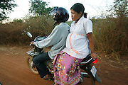 Nut Saroem aged only 19 years old and 8 months pregnant being taken to the local health centre by her husband on a motorbike. Transport ill advised in the west, but here they have little choice. Nout is daughter of a Kruu bush doctor and receiving traditional herbs, was suffering severe preeclampsia and at 8 months pregnant was refered to a clinic by Koeun. The baby was premature, and both lives were saved by Koeun's intervention...Touth Koeun, an ex-Khmer Rouge child soldier turned midwife and trainer, is on the frontline again, but this time campaigning on maternity issues, in Preah Vihear province, Cambodia. The country experiences an extraordinarily high incidence of infant and maternal mortality. The Preah Vihear province, in Cambodia's north, bordering on the Thai border, can be described as an outback rural area, villages often many hours away from a health centre or clinic, and sometimes near the frontline where soldiers and their families are living. Here, Touth Kouen, a locally much respected pioneer and experienced in maternity issues, trains indigenous women, known as 'Traditional Birth Attendants' (TBA's), correct procedures to assist midwives and nurses, to give direct support to mothers and their babies, during ante and post natal periods. Traditional bush medicine and spiritual practices by 'Kruu' bush doctors, involving the killing of endangered species, gathering herbs and plants, whose burnt remains are often ground up into unhealthy potions, and fed to mothers as miracle cures, and postpartum heating, can cause illness and death. The Kruu, and local people in general need to be re-educated, so as to create a healthy nurturing environment for mothers and their babies. Preah Vihear Province, Cambodi