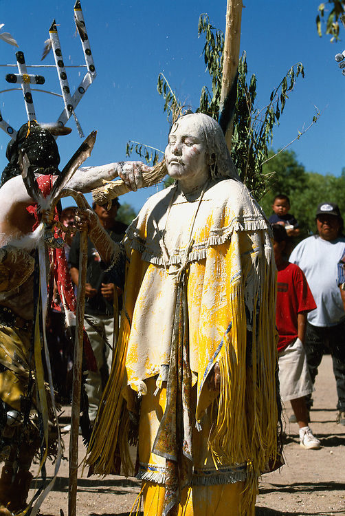 An Apache girl is painted white with sacred clay and corn meal during her Sunrise Dance, a first menstruation rite, on the San Carlos Apache Indian Reservation in Arizona, USA. She is painted by a Mountain Spirit (Gaan) or Crown Dancer, and the staff in her hand symbolises longevity. The painting of the girl is both a blessing and an enactment of certain parts of the Apache creation myth. During the rites the girl becomes Changing Woman, a mythical female figure, and comes into possession of her healing powers. The rites are supposed to prepare the girl for adulthood and to give her a long and healthy life without material wants.