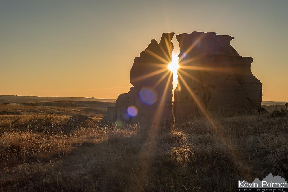 The sun sets in between sandstone pillars in Medicine Rocks State Park.