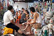 Stall owners in the indoor antique market in Yu Yuan Garden, downtown Shanghai. The pots and ceramics being sold by this family business on the top floor of the market are not genuine antiques. Many are fakes, which are sold to the more gullible tourists. Genuine antiques can be bought but the prices reflect their age considerably.