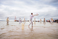 Action gets underway at the annual Bramble Bank cricket match in the middle of the sea. The eccentric game involves members of the Royal Southern Yacht Club in Hamble playing against the Island Sailing Club from Cowes on the Brambles, a patch of sand in the Solent, only visible for a few minutes on the spring tide. The teams take turns in winning. This year the Royal Southern team won and hosted dinner at their club house.<br /> Picture date Monday 31st August, 2015.<br /> Picture by Christopher Ison. Contact +447544 044177 chris@christopherison.com