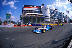 Stock photo of cars speeding down the track in front of the George R. Brown Convention Center during the Houston Texaco Grand Prix