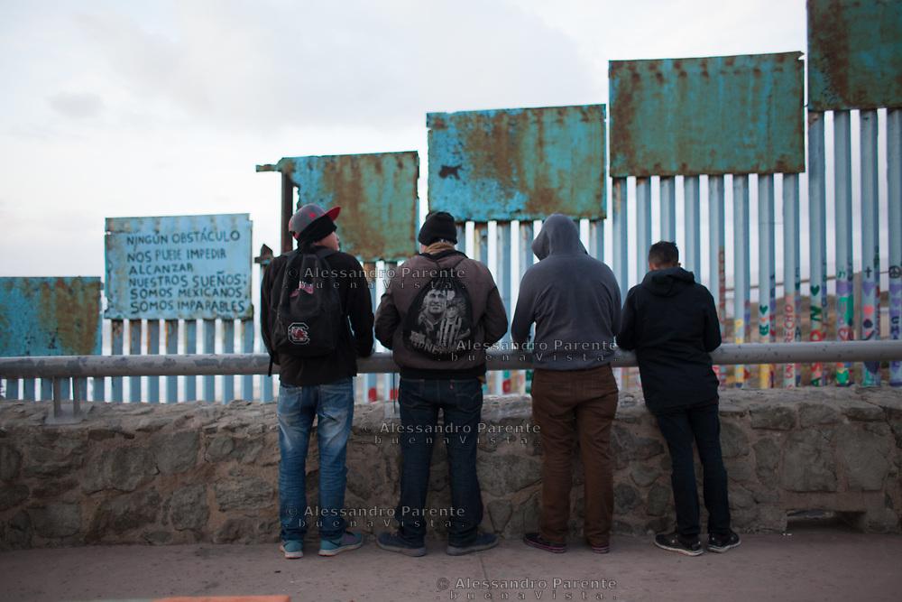 Group of immigrants at the border wall at Tijuana Beach.