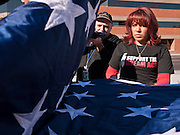 """07 DECEMBER 2010 - PHOENIX, AZ:  YADIRA GAROA and other supporters of the DREAM Act fold up an American flag after picketing the offices of US Sen. John McCain in Phoenix Tuesday. Dolores Huerta, who started working in the civil rights movement in the 1960's, threw her support behind students fasting on behalf of the DREAM Act in front of Sen. John McCain's office Tuesday. The student picked McCain's office because he used to support the DREAM Act. They hope that the US Senate will pass the DREAM Act during its """"lame duck"""" session. The Senate debated and defeated similar legislation just before the November general election.   PHOTO BY JACK KURTZ"""