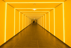 Interior of passageway lit by yellow strip lights under government buildings in Berlin Germany