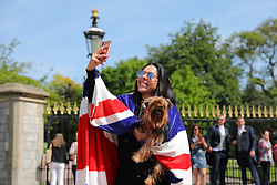 © Licensed to London News Pictures. 18/05/2018. London, UK. A woman wearing a Union Jack flag takes a selfie outside Windsor Castle on the eve of the Royal Wedding. Prince Harry and Meghan Markle are to be married in Windsor tomorrow, Saturday 19 May 2018. Photo credit: Rob Pinney/LNP