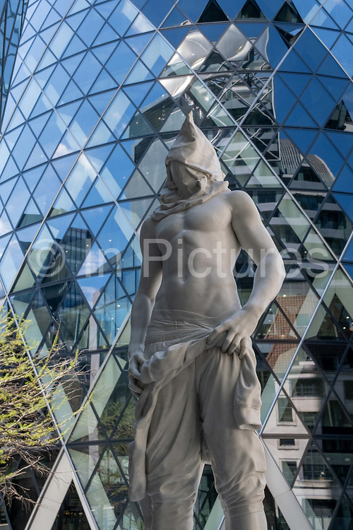 Beneath the Swiss Re building aka the Gherkin is the sculpture artwork entitled Site Of The Fall: Study of the renaissance garden: Action 180: At 9:15 am Sunday 28th May 1967 by Reza Aramesh, on 29th July 2020, in the City of London, England. This piece of art is one of a series of 12 sculptures that form the body of work titled 'Site of the Fall – Study of a Renaissance Garden'. From research on reportage images of the Vietnam war, a single composition was selected, the image of which has been reconstructed through a process of rendering based on live subjects. Hand carved Carrara marble depicts the subject as larger than life. The plinth is a site-specific design to communicate with the environment of where it's situated.