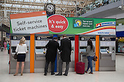 BUYING TICKETS FROM THE AUTOMATED TICKET MACHINES, Royal Ascot racegoers at Waterloo station. London. 19 June 2013.
