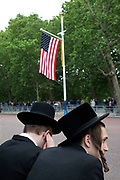 On the first day of the state visit by US President Donald Trump, two young Jewish men wait along The Mall by the US flag on 3rd June 2019 in London, United Kingdom.