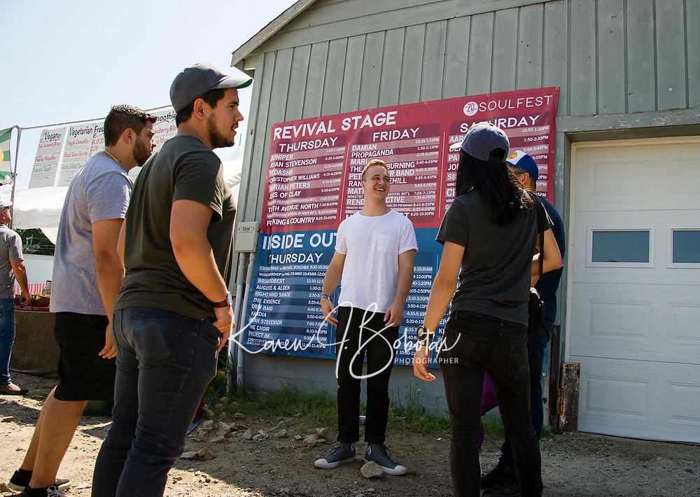 Visitors check out the band schedule for Soulfest Weekend as bands begin to take their stages on Thursday afternoon.  (Karen Bobotas/for the Laconia Daily Sun)