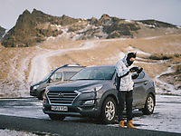 A tourist flying his drone standing by his rental car at a parking lot near the church of Vík, south Iceland.