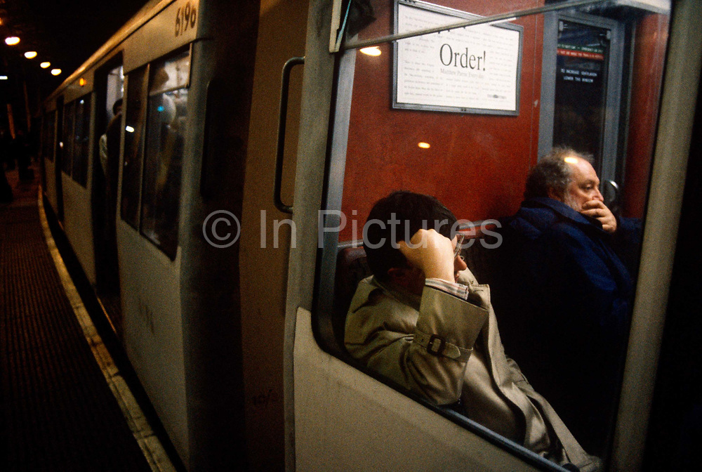 """During the morning rush-hour at Bank underground station in the heart of London's financial district, the grim face of 90s tube travel is seen here in a wide landscape of rounded tunnel and the curve of the station platform. Weary Londoners sit waiting for the doors to close and the hot air to seal them inside the small space, men and women press against each other in a claustrophobic journey along the Central Line. The Central line is a London Underground line, coloured red on the tube map. It is a deep-level """"tube"""" line, running east-west across London, and, at 76 km (47 mi). Incorporated in 1891 it is today the longest Underground line and also the busiest with around 260 million passengers a year."""