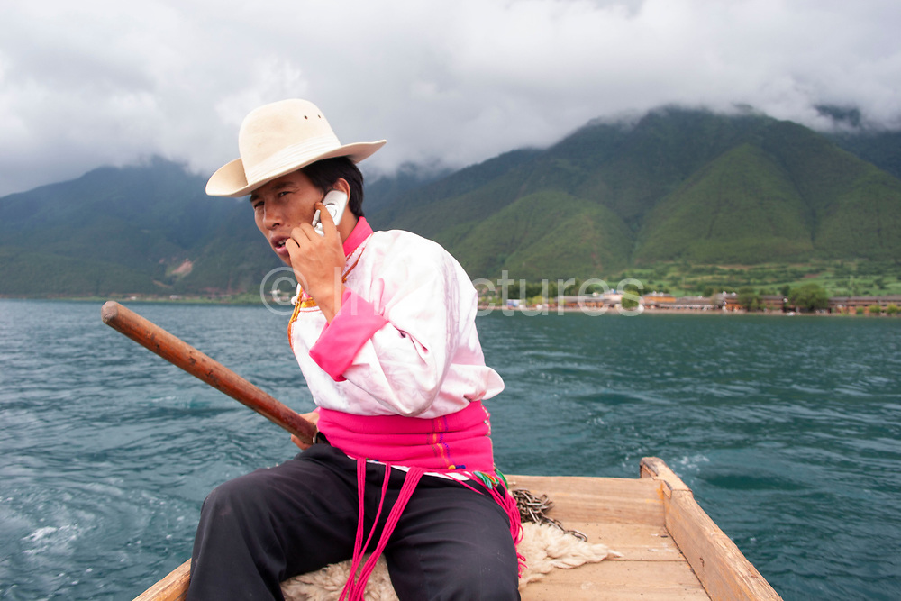 Mo Suo minority man in traditional dress takes a call on his cell phone whilst rowing tourists to a nearby island on Lugu Lake, Yunnan, China. Mo Suo are one of approximately 56 different minorities which live in Yunnan, a temperate south eastern province of China in the foothills of the Himalayas.